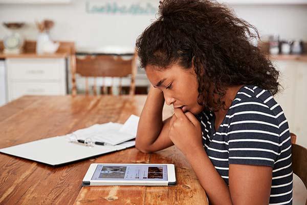 Teenager being bullied online looking at tablet
