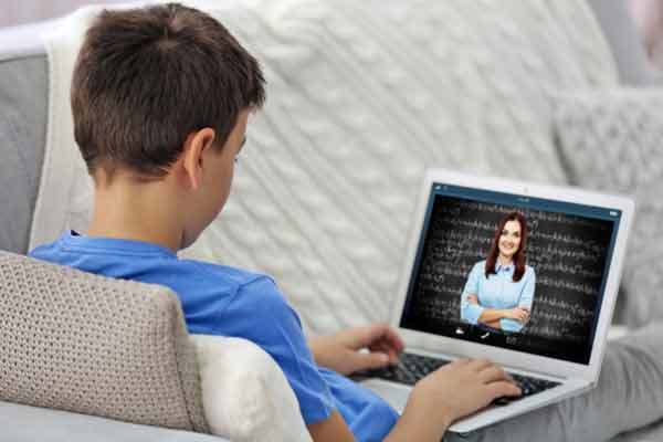 Boy with online tutor on screen